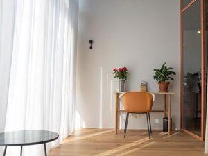 Praktijkruimte, 15 m2 Zitje met houten meubels Zalmroze stalen wand Houten vloer